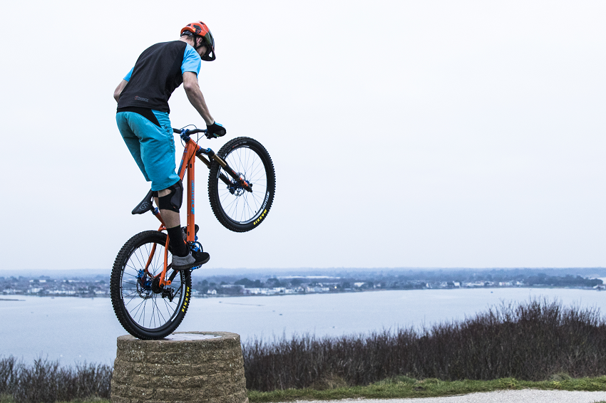 Ben Moore doing balancing on his bike's back wheel at Hengistbury Head