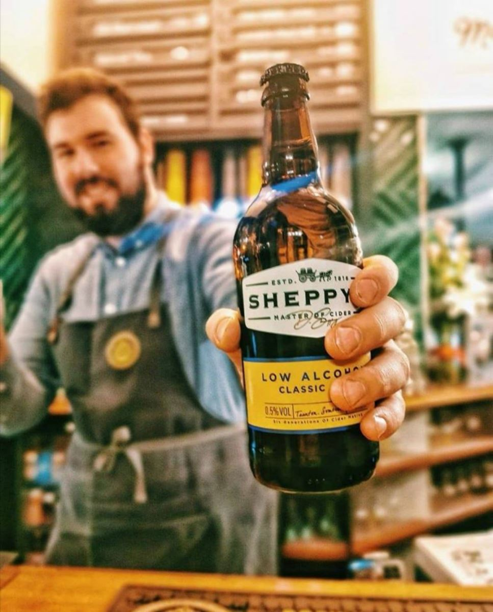 A bartender in the Bournemouth branch of Brewhouse and Kitchen holding a Sheppy low-alcohol beer.