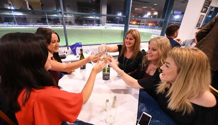 Group of friends toasting at the Poole Greyhound races