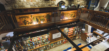 Library in historic building pictured, books and exposed brickwork