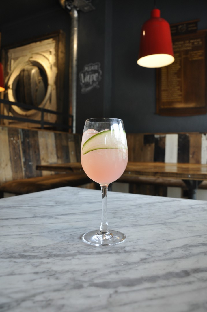 An image of a light pink drink called a Kiss, standing on a table in the Dancing Moose in Poole. A green leaf sits decoratively within the glass