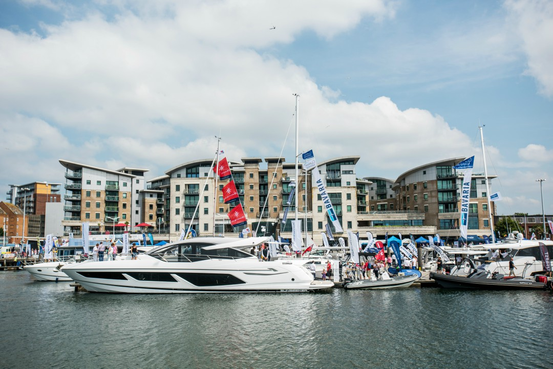 A yacht sits prominently in Poole Harbour over the weekend of the Boat Show, with a crowd milling in the background