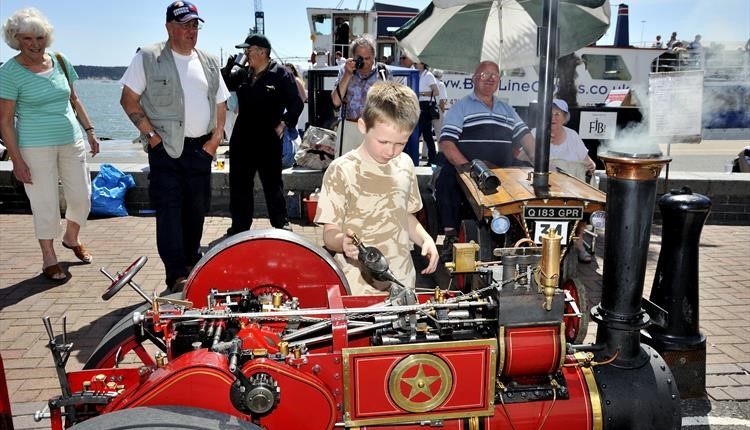 A child fascinated by a small steam engine at Poole Quay