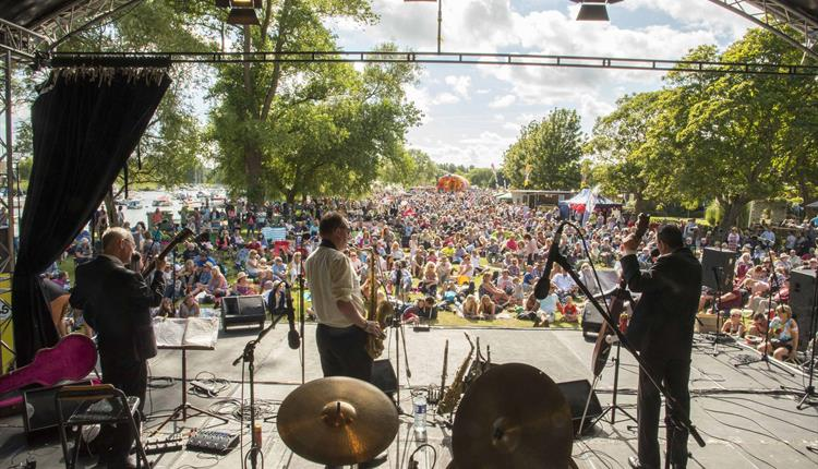 An image looking out between a jazz band towards a large crowed on a sunny day at Stompin' on the Quomps in Christchurch.