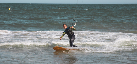 Man in wetsuit kitesurfing in the sea