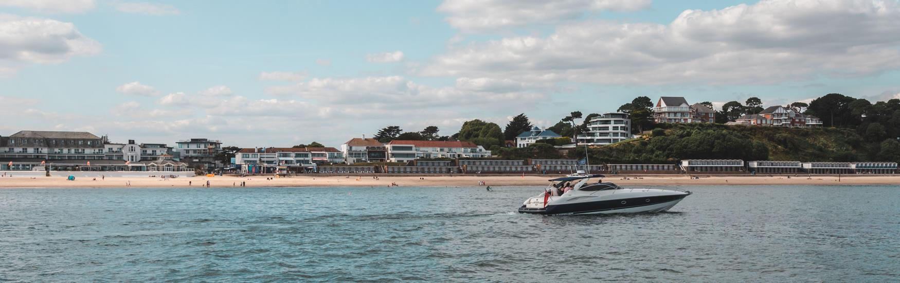 Speedboat pictured travelling along the coast, Sandbanks beach in the  background.