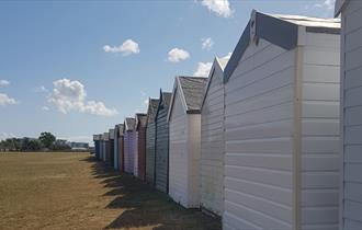 Colourful array of beach huts lined up along Hamworthy park in Poole
