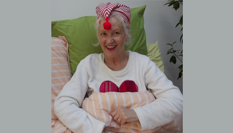 Michele O'Brien wearing a stripey night cap ready to read Sunday night Bedtime Stories from her isolation inspiration station.