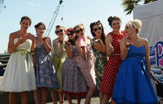 Ladies line up on Poole Quay in vintage clothes