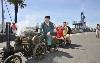 Man sat on mini steam engine.