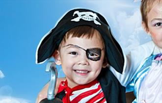 two children pictured in pirate and princess outfits.