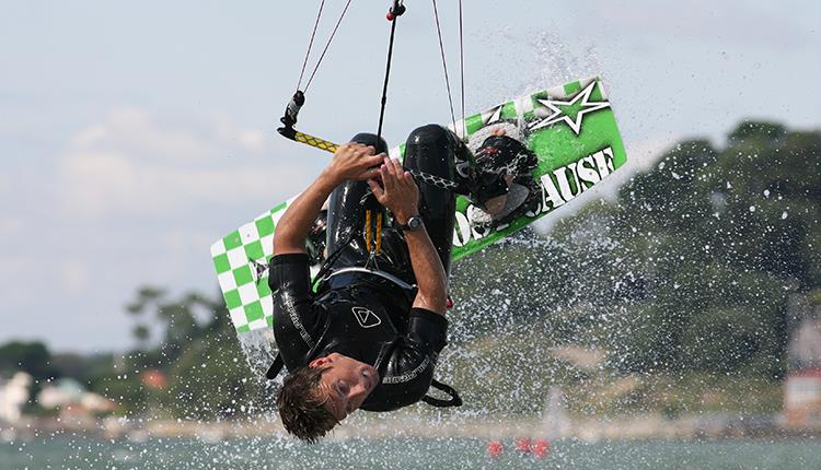 A kitesurfer attempting a backflip in Poole Harbour