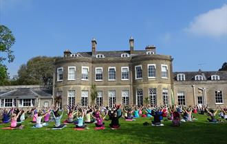 People doing yoga on the lawn in front of Upton House