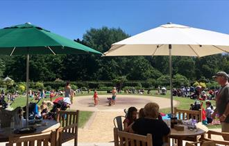 Visitors sat in the sun enjoying the summers day in the parks garden