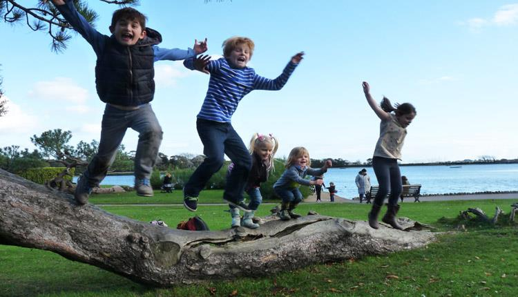 Kids having fun and jumping off a tree at Poole park